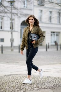 Девушка в болотной куртке бомбер, черных джинсах, в черном топе и с сумкой в руках