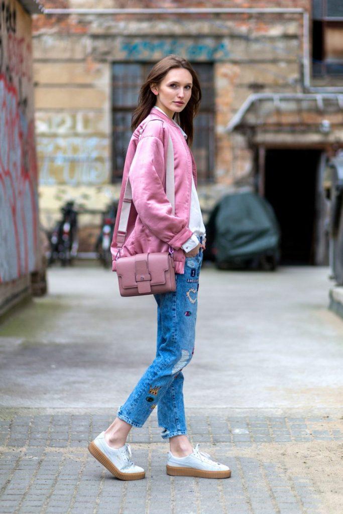 Девушка в розовом бомбере на улице с розовой сумкой.