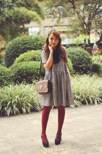 Девушка в сером платье и в бордовых колготках.