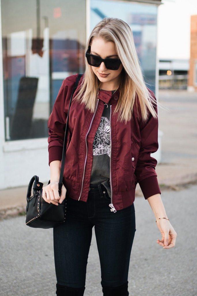 Девушка в темных очках, в модной футболке и в бордовом бомбере с сумкой на плече