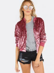 Девушка в бархатном бомбере розового цвета и в коротких шортах.