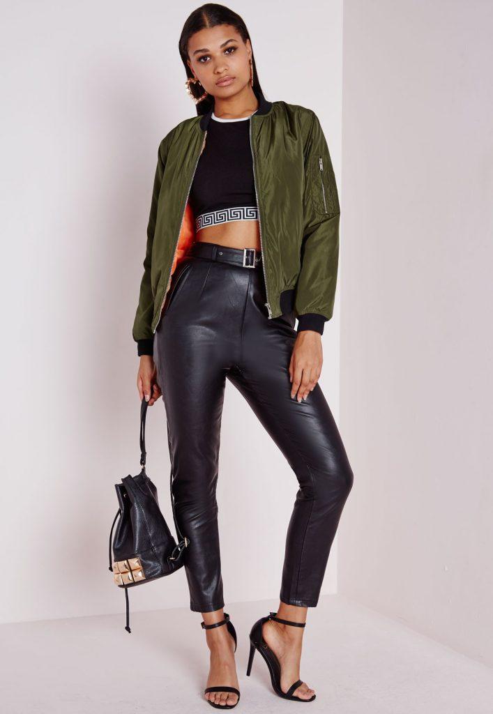 Девушка с сумкой в руках, в бомбере цвета хаки и в кожанных штанах.