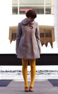 Девушка в сером пальто и в желтых колготках.