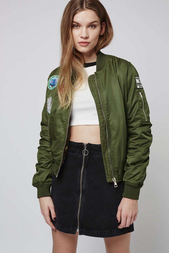 Девушка в зеленом бомбере и в джинсовой юбке.