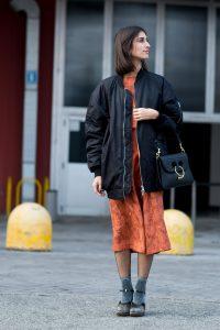 Девушка в оранжевом платье,в удлиненном бомбере на улице.