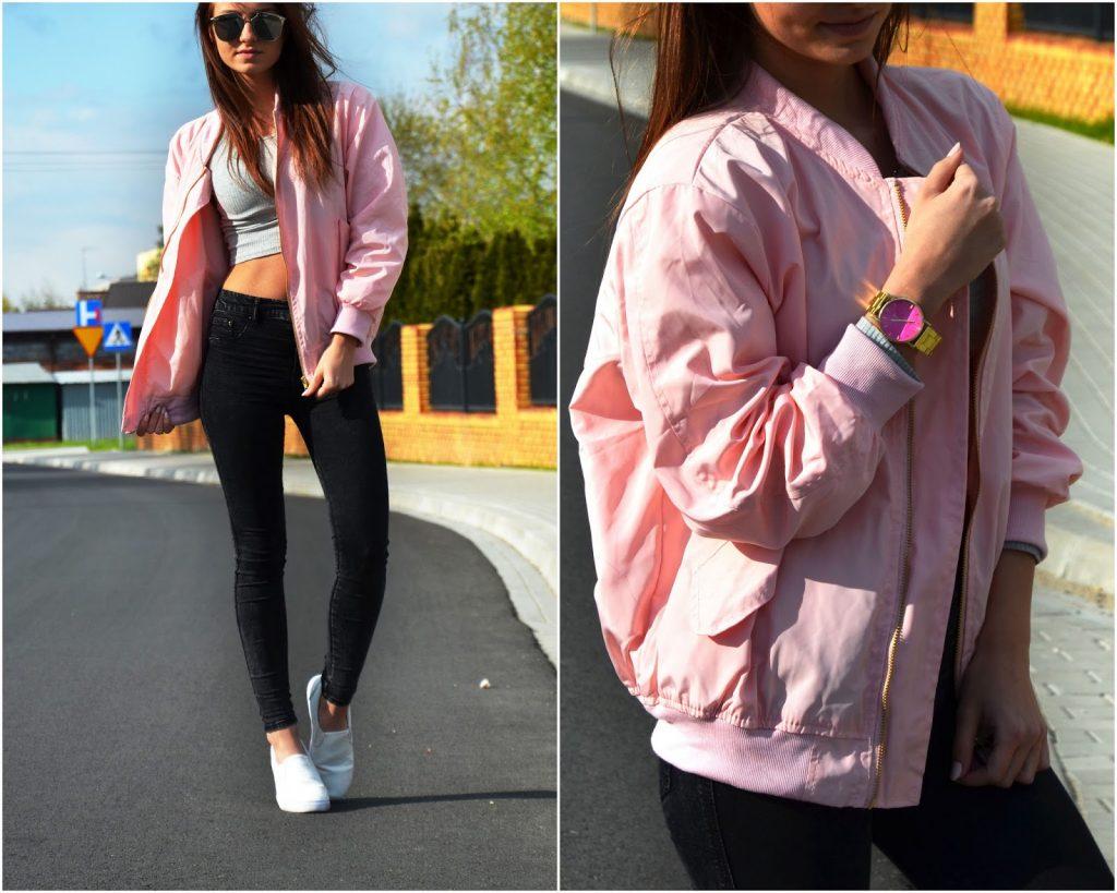 Девушка в розовом бомбере, в темных брюках, в темных очках.