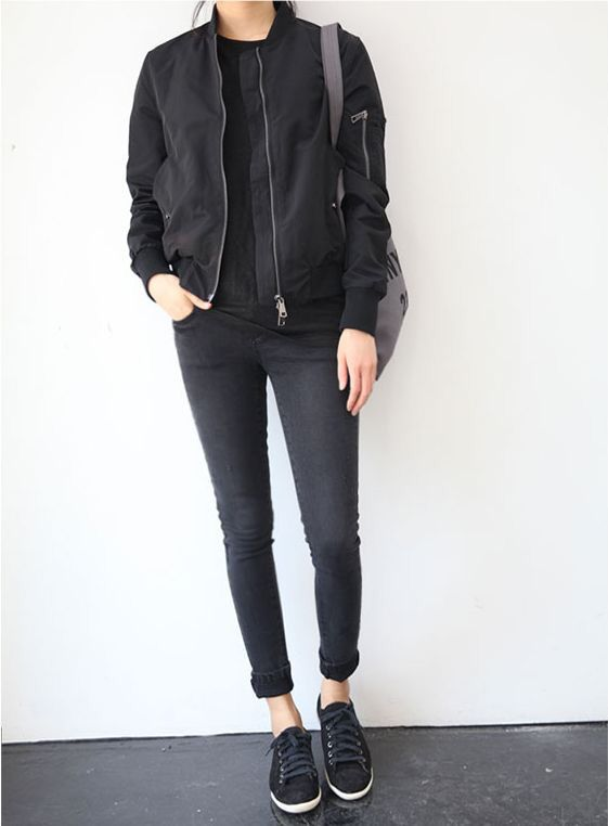 Девушка у белой стены, в черном бомбере, с серой сумкой на плече, в черных брюках и в черных кедах.
