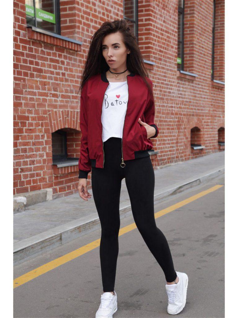 Девушка в бордовом бомбере, в белой футболке в черных леггинсах