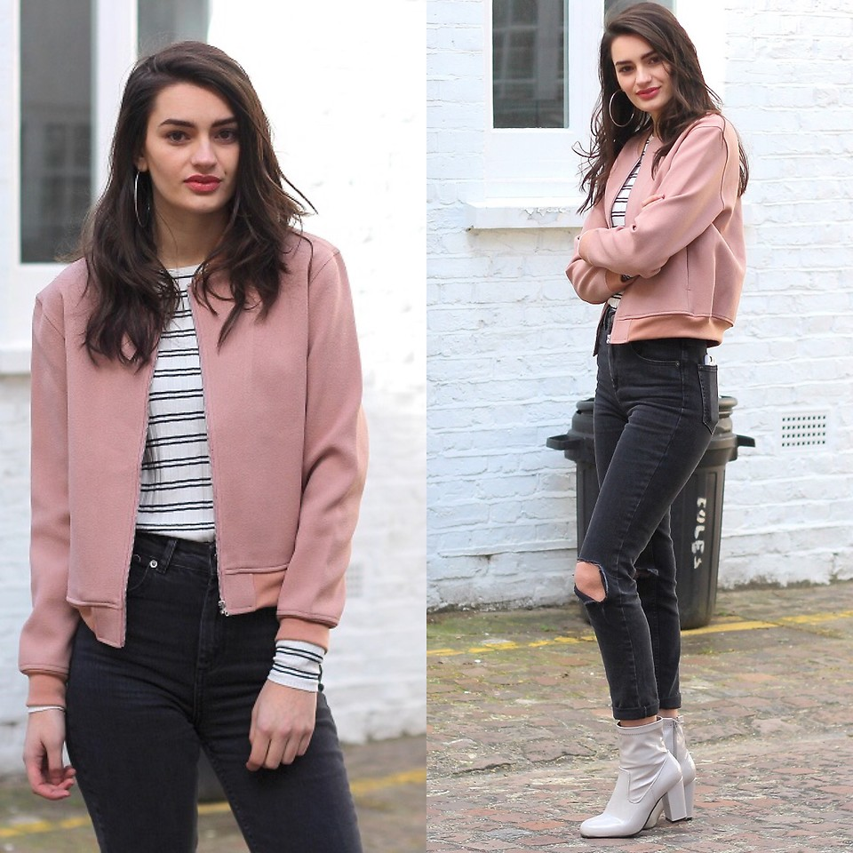 Девушка в розовом бомбере и в серых кожаных ботильонах.