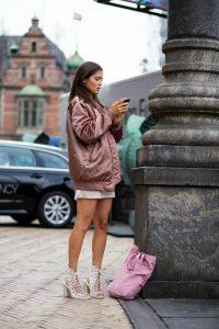 Девушка на улице в бежево-розовом удлиненном бомбере.