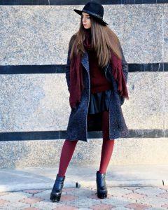 Девушка надета в пальто и в бордовых чулках.
