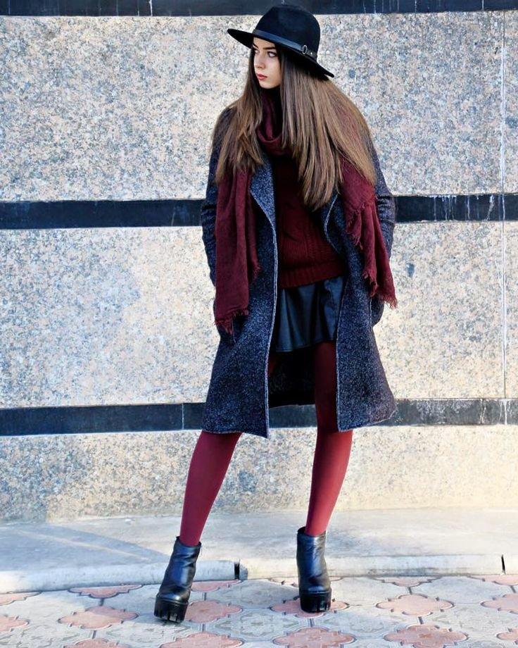 Девушка надета в пальто и в бордовых колготках.
