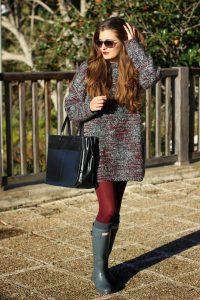Девушка в темных очках с сумкой в руке, в бордовых колготках.