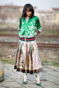 Девушка в шелковом зеленом бомбере на улице.