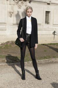 Девушка в кожаных шортах с черными колготками.