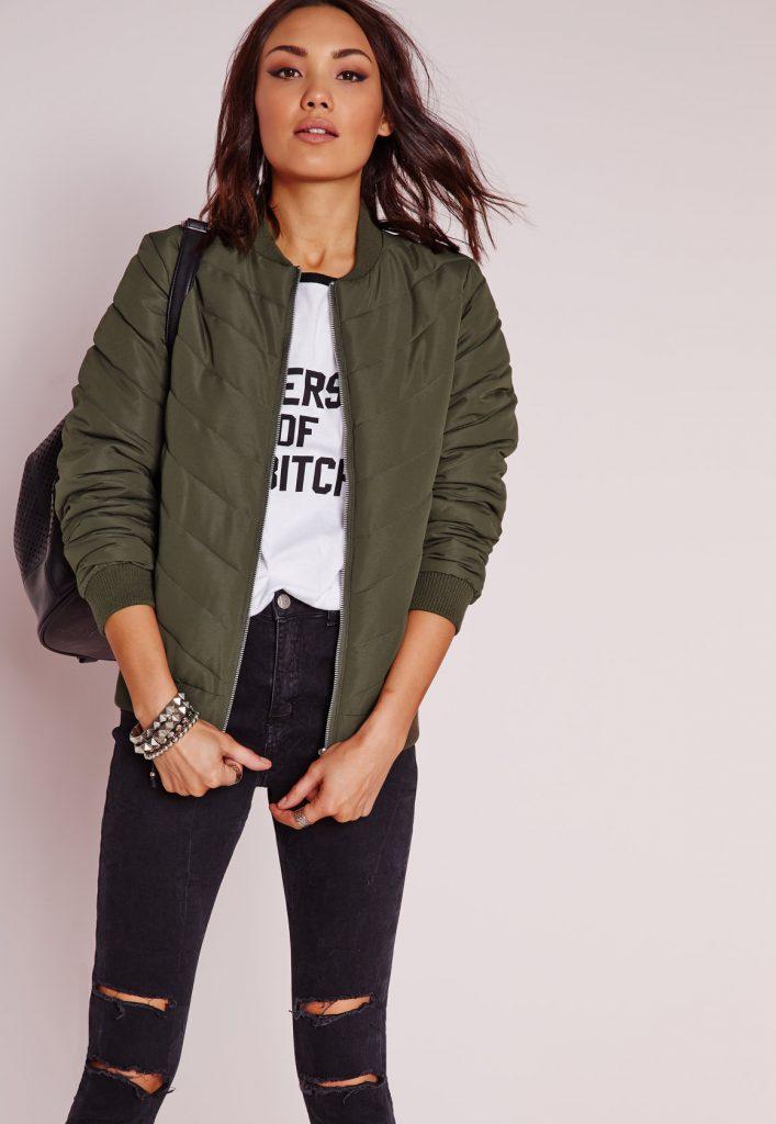 Девушка с темной сумкой, в модной футболке и в рваных джинсах.